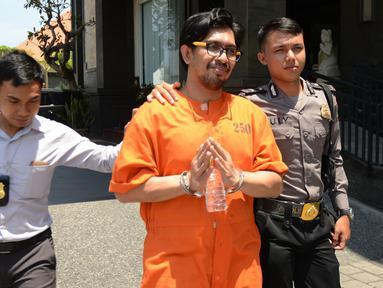 Mohd Husaini Jaslee dari Malaysia dikawal polisi setelah konferensi pers menyusul penahanannya di kantor pabean di Bandara Ngurah Rai, Denpasar, Bali (4/10). Jaslee ditangkap setelah membawah pil ekstasi di dalam tas laptopnya. (AFP Photo/Sonny Tumbelaka)
