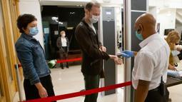 Sejumlah penonton menjalani pengecekan suhu tubuh sebelum memasuki sebuah teater di Moskow, Rusia, pada 3 September 2020. Teater-teater di Moskow membuka kembali musim pertunjukan setelah beberapa bulan ditutup akibat pandemi COVID-19. (Xinhua/Alexander Zemlianichenko Jr)