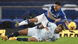 Bek Chelsea, Reece James (bawah), menjatuhkan gelandang Everton, Allan, dalam laga lanjutan Liga Inggris 2020/21 pekan ke-12 di Goodison Park Stadium, Sabtu (12/12/2020). Chelsea kalah 0-1 dari Everton. (AFP/Peter Powell/Pool)