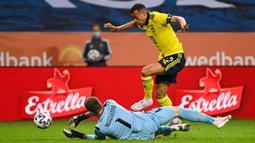 Pemain Swedia Robin Quaison bersaing dengan kiper Armenia David Yurchenko pada pertandingan persahabatan jelang Euro 2020 di Solna, Swedia, Sabtu (5/6/2021). Swedia menang 3-1. (Jonathan NACKSTRAND/AFP)