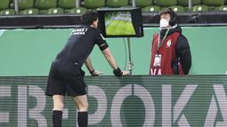 Wasit Manuel Grafe memeriksa rekaman VAR dalam laga semifinal DFB Pokal antara Werder Bremen melawan RB Leipzig di Weserstadion, Bremen, Jumat (30/4/2021). Werder Bremen kalah 1-2 dari RB Leipzig melalui babak perpanjangan waktu. (AP/Carmen Jaspersen/Pool)