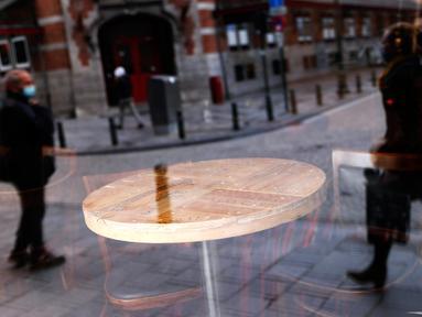 Refleksi orang-orang terlihat dari jendela depan sebuah bar yang tutup di pusat kota Brussel, Belgia, Kamis (8/10/2020). Brussels pada Rabu, 7 Oktober 2020, memutuskan menutup semua bar, ruang dansa, dan kafetaria selama sebulan sebagai upaya membendung lonjakan COVID-19. (AP Photo/Francisco Seco)