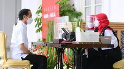 Presiden Joko Widodo atau Jokowi menjalani pendaftaran dan verifikasi data saat mengikuti vaksinasi COVID-19 di Istana Merdeka, Jakarta, Rabu (13/1/2021). Vaksinasi ini jadi titik awal vaksinasi nasional sebagai upaya penanganan pandemi COVID-19. (Biro Pers Sekretariat Presiden/Muchlis Jr)