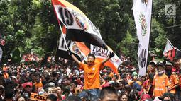 Jakmania mengibarkan bendera Persija saat penyerahan piala Liga I di depan Balai Kota, Jakarta, Sabtu (15/12). Persija kembali meraih juara Liga Indonesia setelah 17 tahun. (Liputan6.com/Herman Zakharia)