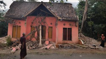 Warga melihat rumah yang rusak usai gempa melanda Pandeglang, Banten, Sabtu (3/8/2019). Menurut data sementara BPBD, sebanyak 106 unit rumah di Kabupaten Pandeglang dan Lebak rusak usai gempa Banten berkekuatan magnitudo 6,9. (RONALD SIAGIAN/AFP)