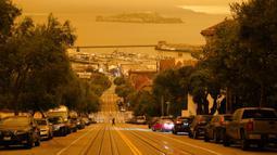 Seorang pria melintasi Hyde Street dengan Pulau Alcatraz dan Fisherman's Wharf terlihat pada latar belakang di San Francisco, Amerika Serikat, Rabu (9/9/2020). Kebakaran hutan di seluruh Barat mengakibatkan langit San Francisco hingga Seattle berwarna oranye yang menakutkan. (AP Photo/Eric Risberg)