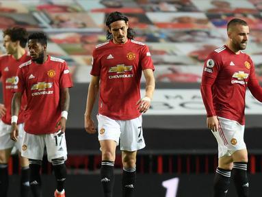 Striker Manchester United, Edinson Cavani (tengah) dan kawan-kawan tertunduk kecewa usai kebobolan gol ketiga saat melawan Liverpool dalam laga lanjutan Liga Inggris 2020/2021 pekan ke-35 di Old Trafford, Kamis (13/5/2021). Manchester United kalah 2-4 dari Liverpool. (AFP/Michael Regan/Pool)