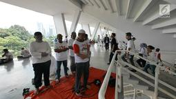 Pendukung capres dan cawapres Joko Widodo (Jokowi)-Ma'ruf Amin menjalankan ibadah menjelang kampanye akbar di Stadion Utama GBK, Senayan, Jakarta, Sabtu (13/15). Kampanye yang diisi dengan konser musik dari ratusan selebritas bertajuk Konser Putih Bersatu. (Liputan6.com/Herman Zakharia)