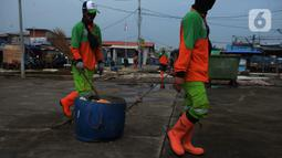 Petugas dari Dinas Lingkungan Hidup DKI Jakarta membawa sampah di Pelabuhan Kali Adem, Muara Angke, Jakarta, Rabu (6/1/2021). Dalam sehari, sampah pesisir Teluk Jakarta Utara bisa terangkut sekitar 7 kubik sampah plastik yang terbawa dari sungai maupun arus laut. (merdeka.com/Imam Buhori)