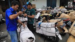 Pekerja membungkus sepeda motor yang akan dikirim di Stasiun Pasar Senen, Jakarta, Selasa (5/6). Jasa pengiriman motor ke daerah meningkat dua kali lipat jelang arus mudik dan Hari Raya Idulfitri 2018. (Liputan6.com/Arya Manggala)