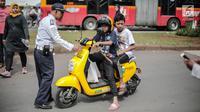 Petugas Dishub mensosialisasikan kepada pengendara sepeda motor listrik Migo saat melintasi CFD di kawasan Bundaran HI, Jakarta, Minggu (17/2). Penyewa sepeda motor listrik dihimbau untuk tidak melintasi jalan raya. (Liputan6.com/Faizal Fanani)