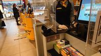 Petugas supermarket terutama bagian kasir wajib menggunakan sarung tangan plastik dan dipasang kaca ektra agar menjaga jarak antara penguntung dan bagian kasir saat melakukan pembayaran ( Foto : Yuke Mayaratih)