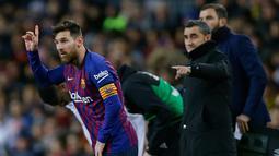 Pemain Barcelona, Lionel Messi (kiri) memasuki lapangan saat akan menghadapi Valencia dalam lanjutan Liga Spanyol di Camp Nou, Spanyol, Minggu (3/2). Dua gol Messi membuat pertandingan berakhir 2-2. (AP Photo/Manu Fernandez)