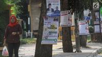 Pejalan kaki melintas dekat Alat Peraga Kampanye (APK) yang dipasang di pohon kawasan Ciater, Tangerang selatan, Senin (1/4). Pemasangan APK sejumlah caleg yang dipaku di pohon melanggar peratuan KPU Nomor 15 Tahun 2013 tentang tata cara pemasangan APK pemilihan umum. (merdeka.com/Arie Basuki)