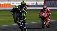 Pembalap Monster Energy Yamaha Valentino Rossi menampilkan wheelie pada latihan bebas ketiga (FP3) MotoGP Valencia di Sirkuit Ricardo Tormo, Sabtu (16/11/2019). Rossi menempati posisi keempat pada FP3 MotoGP Valencia. (PIERRE-PHILIPPE MARCOU/AFP)