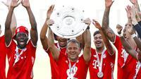 Pelatih Bayern Munchen, Hansi Flick, mengangkat trofi juara Bundesliga usai melawan Wolfsburg di Volkswagen Arena, Sabtu (27/6/2020). Kemenangan itu membuat Bayern kokoh di puncak klasemen sekaligus mengunci gelar juara Bundesliga. (AP/Kai Pfaffenbach)