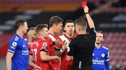 Bek Southampton, Jannik Vestergaard (tengah) menerima kartu merah dari wasit Robert Jones saat melawan Leicester City dalam laga lanjutan Liga Inggris 2020/2021 pekan ke-34 di St Mary's Stadium, Southampton, Jumat (30/4/2021). Southampton bermain imbang 1-1 dengan Leicester. (AFP/Neil Hall/Pool)