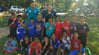 Kiper Arema, Joko Ribowo (kanan), bersama anak-anak dari JRFA di Pati, Jawa Tengah. (Bola.com/Iwan Setiawan)