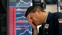 Reaksi pialang Michael Gallucci saat bekerja di New York Stock Exchange, Amerika Serikat, Rabu (11/3/2020). Bursa saham Wall Street anjlok pada akhir perdagangan Rabu (11/3/2020) sore waktu setempat setelah WHO menyebut virus corona COVID-19 sebagai pandemi. (AP Photo/Richard Drew)