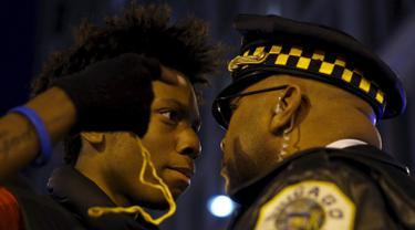 Massa bersitegang dengan polisi saat aksi protes di Chicago, Illinois, Rabu (25/11). Ketegangan rasial memanas setelah rilisnya video seorang polisi kulit putih menembak remaja kulit hitam, Laquan McDonald (17) pada Oktober 2014. (REUTERS/Andrew Nelles)