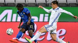 Penyerang Italia, Moise Kean, berebut bola dengan gelandang Bosnia, Muhamed Besic, pada laga UEFA Nations League di  Artemio Franchi, Sabtu (5/9/2020) dini hari WIB. Italia bermain imbang 1-1 atas Bosnia. (AFP/Isabella Bonotto)