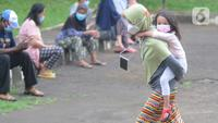 Pasien Covid-19 menggendong seorang anak melintas di halaman Graha Wisata Ragunan, Jakarta, Selasa (15/6/2021). Pemprov DKI memfungsikan kembali Graha Wisata Ragunan sebagai tempat isolasi warga terpapar COVID-19 kategori OTG sejak pekan lalu dan saat ini merawat 117 pasien (merdeka.com/Arie Basuki)