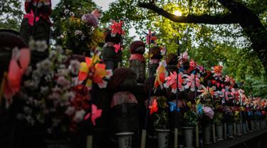 Patung-patung Jizo terlihat di Kuil Zojoji, Tokyo pada 22 Juni 2020. Jizo adalah pelindung dari anak-anak yang belum sempat lahir atau meninggal dalam kandungan dan saat masih bayi. (Photo by Philip FONG / AFP)