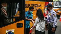 Penumpang menaiki bus sekolah di Kawasan Stasiun Sudirman, Jakarta, Jumat (19/6/2020). Dinas Perhubungan DKI Jakarta telah mengerahkan 50 armada bus sekolah untuk membantu mengurai lonjakan penumpang KRL. (Liputan6.com/Faizal Fanani)