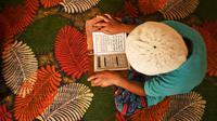 Seorang anak yatim Muslim mengenakan masker bertadarus sambil menjaga jarak sosial di dalam pusat panti asuhan selama bulan suci Ramadan di Srinagar (11/5/2020). (AFP/Tauseff Mustafa)