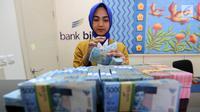 Petugas teller Bank BJB menghitung uang di kantor Bank BJB Cabang Kebayoran Baru, Jakarta Selatan. (Liputan6.com/Fery Pradolo