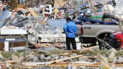 Seorang pria mencari barang-barang yang bisa dia selamatkan dari tokonya setelah tornado menerjang Cookeville, Tennessee, Amerika Serikat, Selasa (3/3/2020). Terjangan tornado menyebabkan kerusakan besar pada bangunan, jalan, jembatan, dan pusat bisnis. (AP Photo/Mark Humphrey)