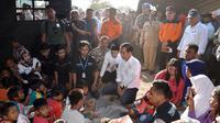 Presiden Joko Widodo atau Jokowi bersama Gubernur NTB Tuan Guru Bajang (TGB) Zainul Majdi berbincang anak-anak saat mengunjungi korban gempa di Desa Madayin, Sambelia, Lombok Timur, NTB, Senin (30/7). (Agus Suparto/Indonesian Presidential Palace/AFP)