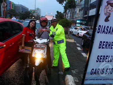 Seorang petugas bersama Pandu Jalan Fullo melakukan sosialisasi tertib berlalu lintas di kawasan perempatan Cideng, Jakarta, Senin (23/2). (Liputan6.com/Johan Tallo)