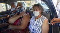Tiga orang dalam mobil mendapatkan suntikan vaksin COVID-19 Sinovac sebagai bagian dari program vaksinasi prioritas untuk lansia di lokasi drive-thru yang didirikan di tempat parkir stadion sepak bola Pacaembu, Sao Paulo, Brasil, Rabu (3/3/2021). (AP Photo/Andre Penner)