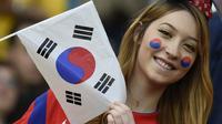 Seorang wanita cantik pendukung Korea Selatan mengibarkan bendera Korsel saat tim kesayangannya berlaga melawan Aljazair di Porto Alegre pada 22 Juni 2014 (AFP PHOTO/PHILIPPE DESMAZES)
