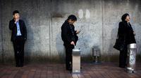 Warga saat merokok di smoking area yang disediakan di Naka-Meguro, Tokyo (10/3). Jepang adalah salah satu negara yang memberlakukan aturan ketat bagi para perokok di tempat umum. (AFP Photo/BEHROUZ MEHRI)
