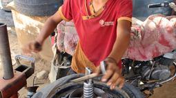 Seorang anak memperbaiki ban di distrik Abs utara di provinsi Haji Yaman, (8/5). Menurut badan anak-anak PBB jumlah anak-anak tanpa akses ke pendidikan menjadi dua juta, karena anak di bawah umur direkrut untuk bertempur. (AFP Photo/Essa Ahmed)
