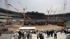 Wartawan mengunjungi New National Stadium yang dalam pembangunan pada tur media ke sejumlah venue Olimpiade Tokyo 2020 di Tokyo, Rabu (18/7). Dewan Olahraga Jepang mengatakan proyek ini sudah mencapai 40 persen jelang upacara pembukaan. (AP/Koji Sasahara)