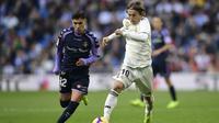 Gelandang Real Madrid, Luka Modric, berusaha melewati gelandang Real Valladolid, Leo Suarez, pada laga La Liga Spanyol di Stadion Santiago Bernabeu, Madrid, Sabtu (3/11). Madrid menang 2-0 atas Valladolid. (AFP/Javier Soriano)