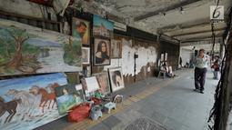 Seorang pria melihat karya lukisan di trotoar Kawasan Glodok, Jakarta, Selasa (15/5). Para pelukis ini menawarkan jasanya dengan kisaran harga Rp150 ribu sampai dengan Rp 5 juta. (Liputan6.com/Herman Zakharia)