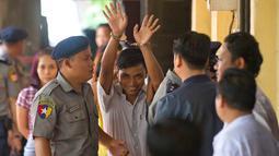 Wartawan Reuters, Kyaw Soe Oo (tengah) dikawal oleh polisi setibanya di pengadilan distrik Yangon, Myanmar, Senin (3/9). Dua jurnalis Reuters dituduh melanggar undang-undang rahasia negara saat menyelidiki kekerasan terhadap Rohingya. (AP/Thein Zaw)
