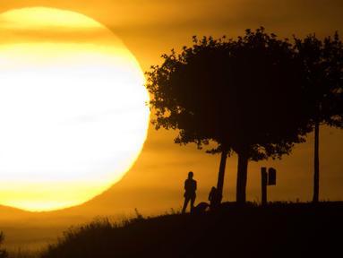 Orang-orang terlihat siluet saat berjalan-jalan selama matahari terbenam di bukit Kronberg di Hannover, Jerman utara (6/8). (AP Photo/Julian Stratenschulte)