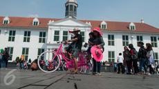Warga berwisata menaiki sepeda kuno di kawasan Kota Tua, Jakarta, Senin (5/1). Meskipun libur panjang akan berakhir, warga tetap memadati kawasan wisata Kota Tua. (Liputan6.com/Gempur M Surya)