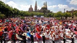 Pasangan menari mengikuti irama musik tradisional mariachi untuk memecahkan Rekor Dunia Guinness di Guadalajara, Meksiko pada 24 Agustus 2019. Sebanyak 882 orang menari dengan kostum tradisional dalam upaya memecahkan rekor dunia untuk kategori tarian rakyat terbesar. (ULISES RUIZ/AFP)