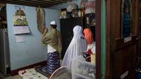 Keluarga Muslim Thailand melaksanakan salat setelah berbuka puasa di ruang tamu rumah mereka di Bangkok, pada 28 April 2020. Banyak tempat ibadah ditutup guna membendung penyebaran Virus Corona COVID-19 ketika Umat Muslim di seluruh dunia menyambut bulan suci Ramadan. (AP Photo/Gemunu Amarasinghe)
