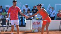 Petenis Serbia , Novak Djokovic bersalaman dengan Olga Danilovic selama pertandingan ganda campuran mereka di sebuah turnamen di Zadar, Kroasia (19/6/2020). Novak Djokovic dan istrinya menderita COVID-19.  (AP Photo/Zvonko Kucelin)