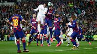 Bek Real Madrid Raphael Varane (kiri tengah) dan pemain Barcelona, Gerard Pique melompat saat berebut bola pada lanjutan pertandingan La Liga di Santiago Bernabeu, Minggu (2/3/2020).  Real Madrid membungkam Barcelona 2-0 dan merebut puncak klasemen dari Barcelona . (AP/Manu Fernandez)