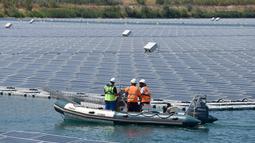 Petugas menggunakan perahu karet memeriksa panel surya fotovoltaik mengapung di kompleks pembangkit listrik O'Mega1 di Piolenc, Prancis selatan (30/7/2019). Pembangkit listrik tenaga surya (PLTS) mengapung pertama di Eropa ini akan beroperasi pada September 2019. (AFP Photo/Gerard Julien)