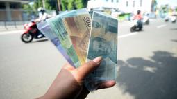 Penjual jasa penukaran uang menawarkan uang baru berbagai pecahan kepada pengguna jalan di kawasan Bintaro Sektor 2, Jakarta Selatan, Selasa (12/05/2020). Pembeli uang kertas baru yang biasanya ramai menjelang Lebaran, kini sepi di tengah pandemi virus corona Covid-19. (merdeka.com/Dwi Narwoko)