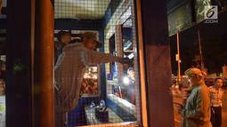 Petugas dibantu warga memperbaiki pos polisi yang sebelumnya dibakar massa saat peringatan Hari Buruh di Yogyakarta, Selasa (1/5) malam. Aksi ini menyebabkan kericuhan antara polisi, warga sekitar dan pendemo. (Liputan6.com/Gholib)